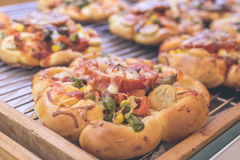Mini pizzas with cheese, tomato, green beans, corn and sausages in the shoppin mall, small italian bakery. Tropical royalty free stock photos