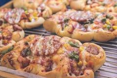 Mini pizzas com queijo, tomate, os feijões verdes, o milho e as salsichas no shopping, padaria italiana pequena tropical foto de stock