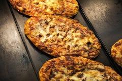Mini pizzas con el salami, el queso y el tomate fotos de archivo