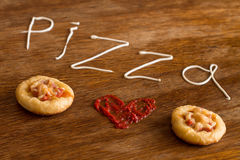 Mini pizzas con la salchicha y el queso en la tabla de madera Imagen de archivo