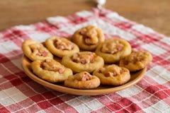 Mini pizzas con la salchicha y el queso en placa anaranjada Imagen de archivo libre de regalías