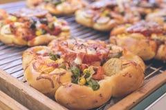 Mini pizzas con queso, el tomate, las habas verdes, el maíz y las salchichas en la alameda de compras, pequeña panadería italiana fotos de archivo libres de regalías