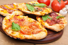 Mini pizzas em uma placa de corte Imagens de Stock