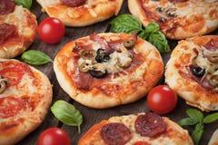 Mini pizzas. With ham, salami, cheese and tomato Royalty Free Stock Photos