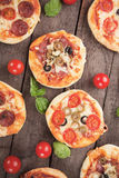 Mini pizzas. With ham, salami, cheese and tomato Stock Photography