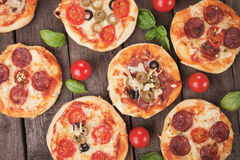 Mini pizzas. With ham, salami, cheese and tomato Royalty Free Stock Photo