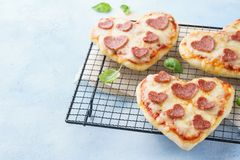 Mini pizzas with heart shaped pepperoni, mozzarella and basil royalty free stock images