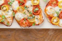 Mini pizzas with mozzarella, cherry tomatoes and basil Royalty Free Stock Photo