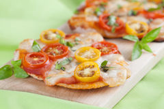 Mini pizzas with mozzarella, cherry tomatoes and basil Stock Image