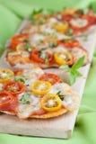 Mini pizzas with mozzarella, cherry tomatoes and basil Stock Photo