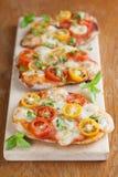 Mini pizzas with mozzarella, cherry tomatoes and basil Royalty Free Stock Image