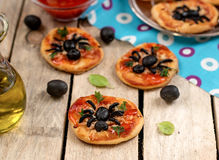 Mini pizzas with olives in shape of spider Royalty Free Stock Images