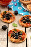 Mini pizzas with olives in shape of spider Royalty Free Stock Image