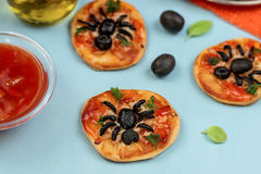 Mini pizzas with olives in shape of spider Stock Photos