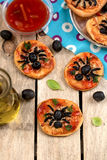 Mini pizzas with olives in shape of spider Stock Photo