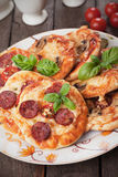 Mini pizzas. With salami, cheese and tomato Royalty Free Stock Images