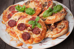 Mini pizzas. With salami, cheese and tomato Stock Photography