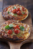 Mini pizzas. Small pizzas with ham, bacon, cheese and tomatoess Royalty Free Stock Photography