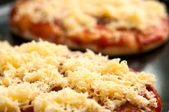 Mini pizzas or small pellets covered with cheese. Close-up Stock Photo
