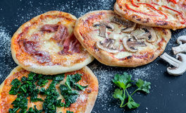 Mini pizzas with various toppings on the wooden board Stock Image