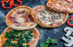 Mini pizzas with various toppings on the wooden board Royalty Free Stock Photos