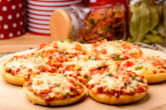 Mini pizzas on wooden board. Stock Photo