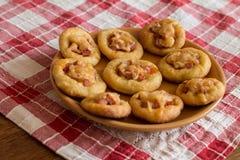 Mini pizze w pomarańcze talerzu na w kratkę tablecloth Zdjęcia Stock