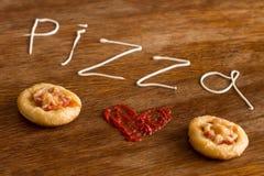 Mini pizze z kiełbasą i serem na drewno stole Obraz Stock