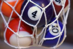 Mini pool table balls. Miniature pool table balls in pocket net Royalty Free Stock Photos