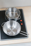 Mini pot et casserole d'acier inoxydable sur le fourneau électrique noir au-dessus de l'OE Photos libres de droits