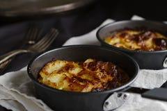 Mini potato gratins on white linen horizontal. Individual mini potato gratins on white linen horizontal royalty free stock photo