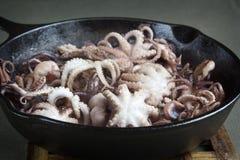 Mini poulpe en cours de torréfaction sur une casserole de fonte Photos libres de droits