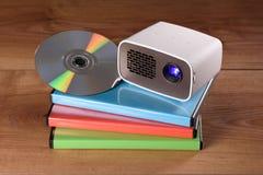 Mini Projector avec des cas de DVD et de DVD sur la table en bois Images stock