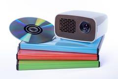 Mini Projector avec le DVD sur des caisses de DVD d'isolement sur le fond blanc Photographie stock libre de droits