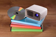 Mini Projector with DVD and DVD cases on wooden table. The Gadget is battery-operated, lamp is on Stock Images