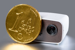 Mini Projector with golden euro coin. For size comparison reflecting on a silver background Stock Image