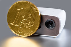 Mini Projector with golden euro coin. For size comparison reflecting on a silver background Royalty Free Stock Photo