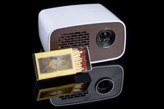 Mini projector with matchbox. For size comparison reflecting on a black background Stock Photo