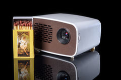 Mini projector with matchbox. For size comparison reflecting on a black background Royalty Free Stock Photography