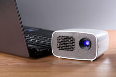 Mini projector with notebook on wooden table. Battery operated mini projector with a laptop on a desk. The transfer of the image is wireless Stock Photo