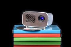 Mini Projetor com o DVD em DVD encaixota refletir no backgro preto Imagem de Stock