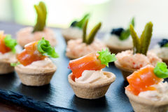 Mini puff pastry tartlets with smoked salmon filling. Royalty Free Stock Images