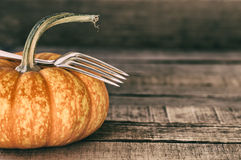 Mini Pumpkin with fork still life on rustic, board background Stock Photo