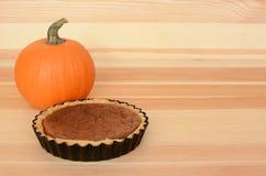 Mini pumpkin pie with orange pumpkin on wood Stock Images