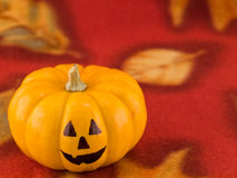 Mini Pumpkins with Funny Faces on a Red Autumn Clo Royalty Free Stock Photography