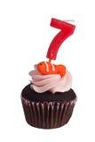 Mini queque com vela do aniversário para a criança de sete anos Imagens de Stock