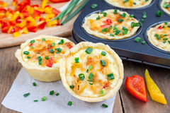 Mini quiche with chicken and bell pepper. On a wooden table Royalty Free Stock Photo