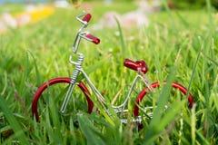 mini- röd leksakcykel på gräs Fotografering för Bildbyråer