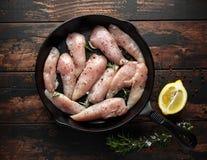 Mini raccordi del petto di pollo crudo in padella rastic del ghisa, padella con le erbe e sale marino fotografia stock libera da diritti