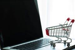 Mini Red Shopping Cart On bärbar dator Royaltyfri Fotografi